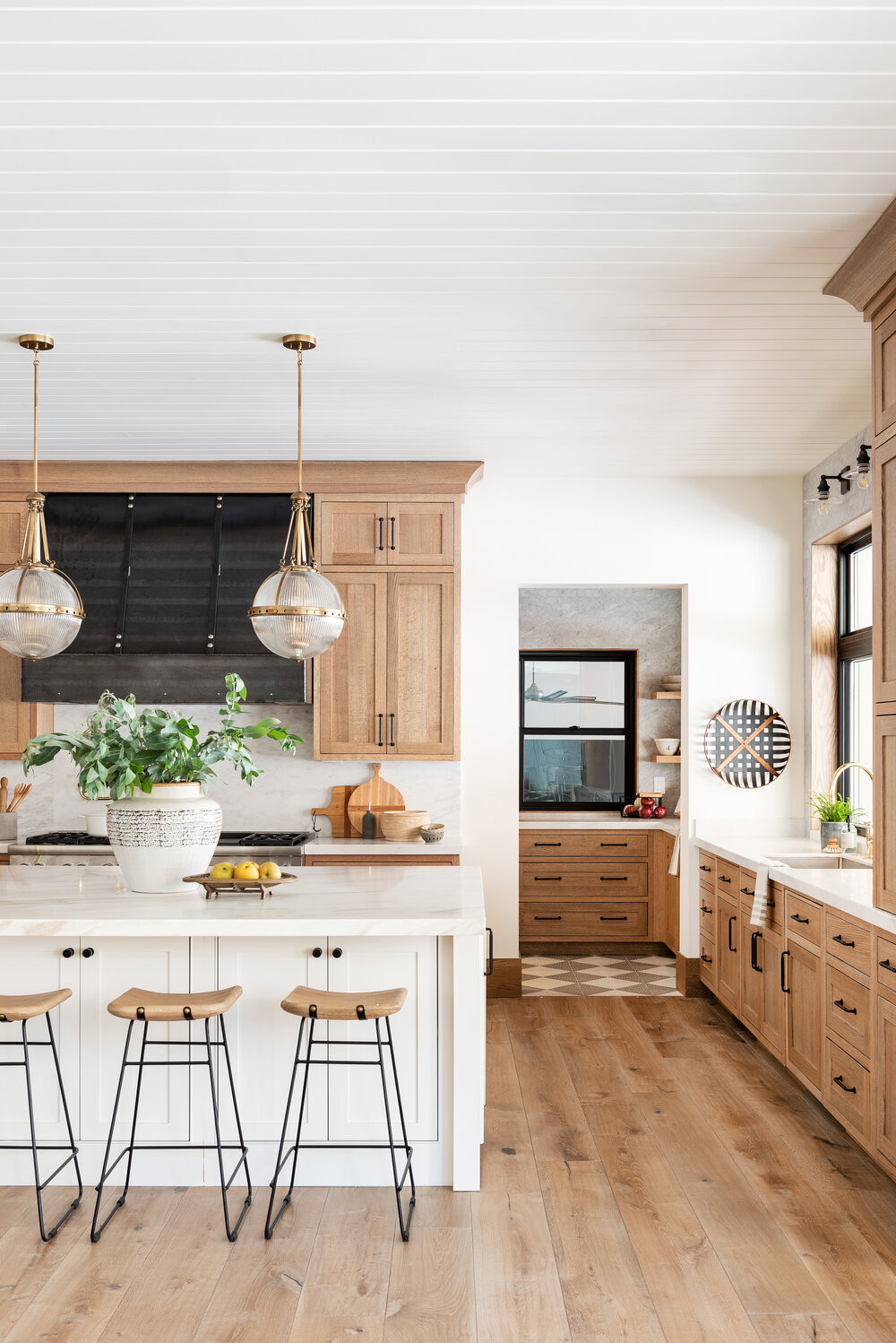 shiplap ceiling glass and brass pendant lights over quartz countertop white cabinets black pulls wooden stools with black metal legs wood cabinets dark metal hood fan vase with green branches black framed windows