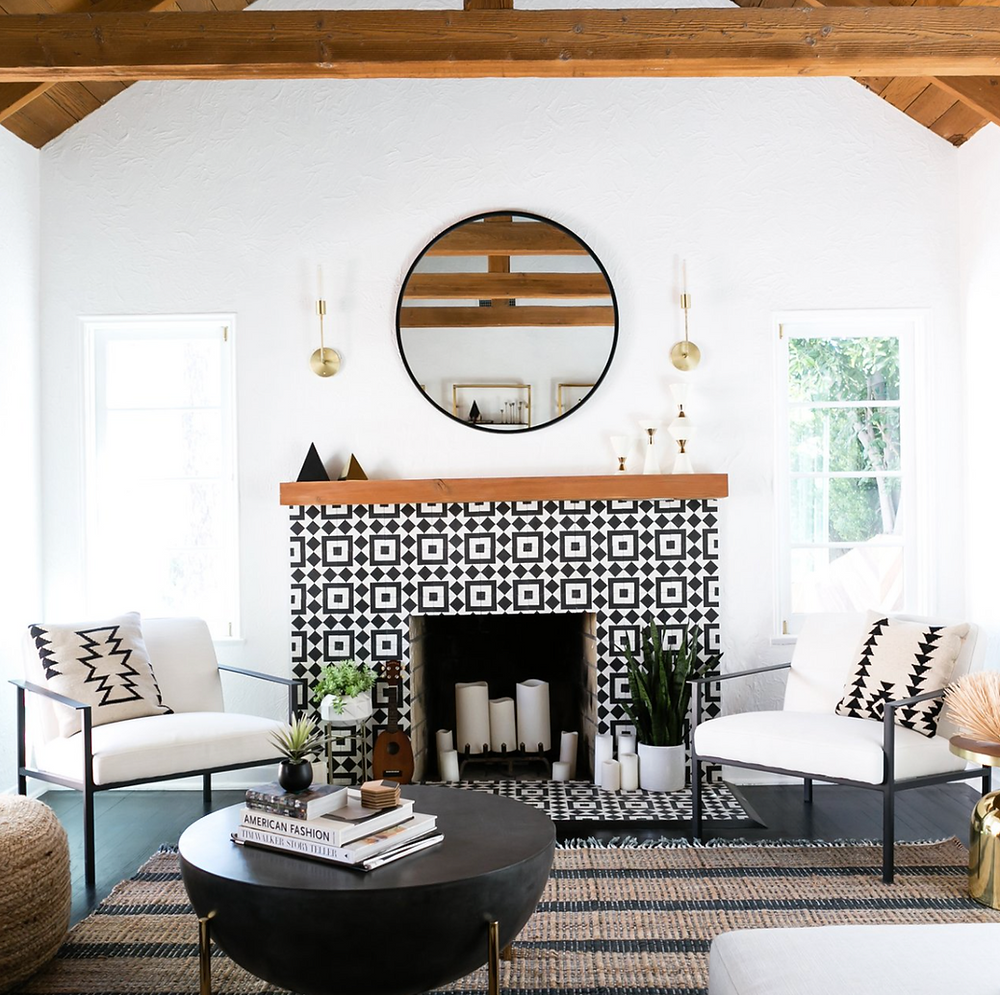 A bold black and white tile fireplace with a wood mantel in the middle of two white chairs in a living room.