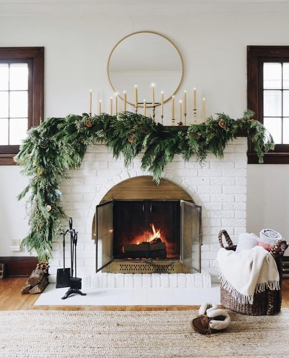A white Christmas holiday fireplace mantel decorated with greenery, candles and a mirror with a basket of blankets for a modern and cozy feel.