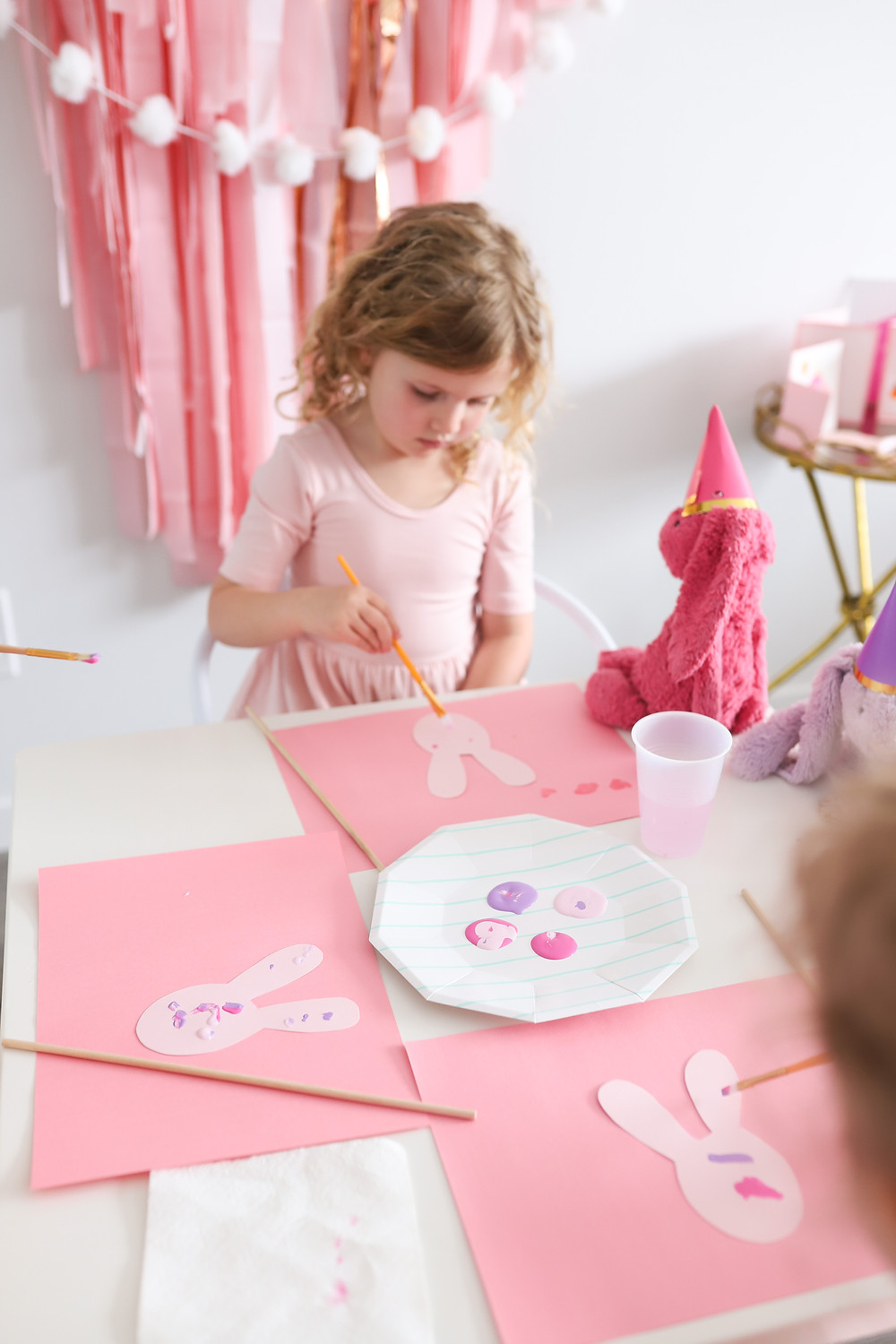 A little blonde girl sitting at a table at a birthday party painting a pink and purple bunny craft.