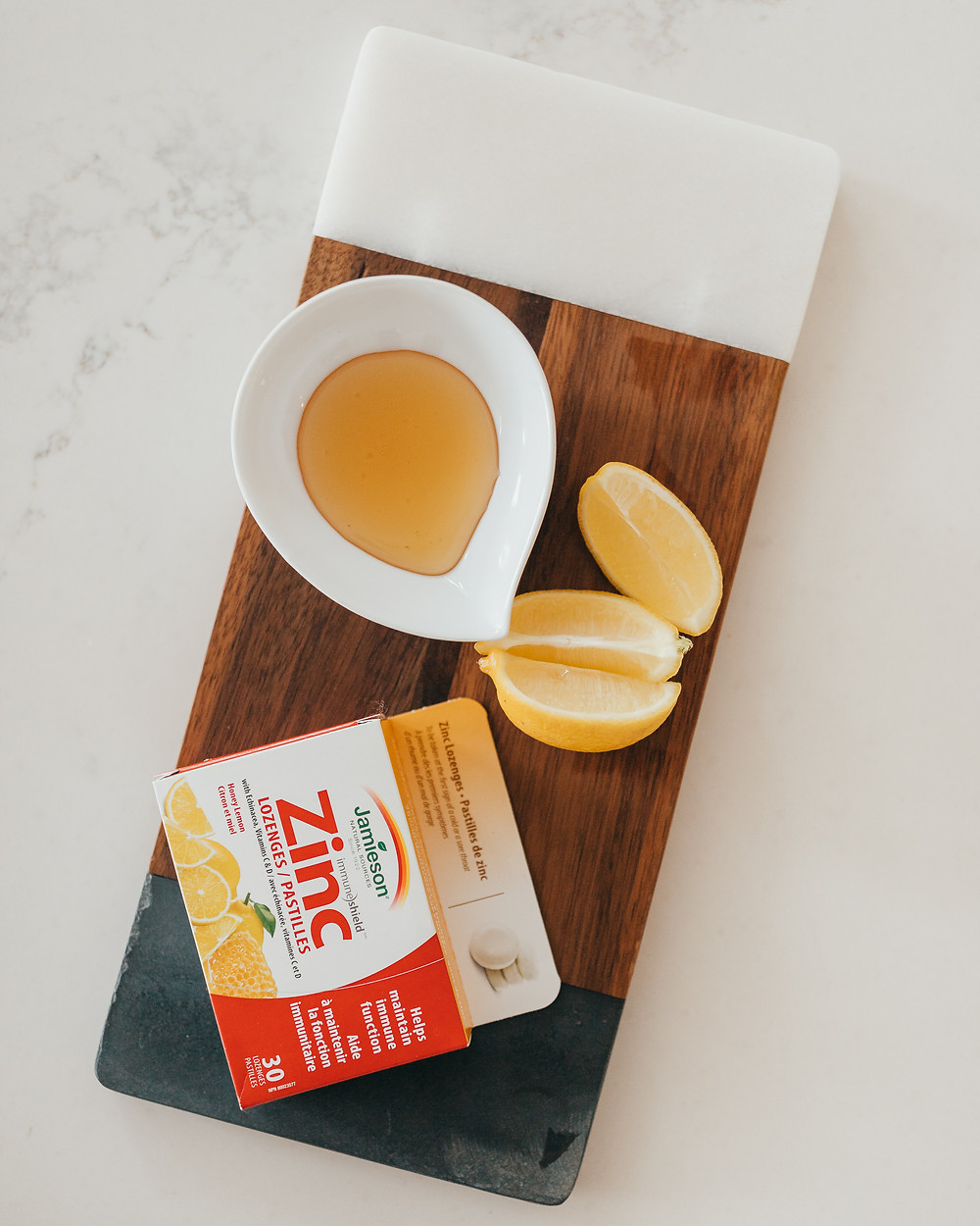 A box of zinc lozenges sitting on a wooden serving platter next to some honey and lemons.