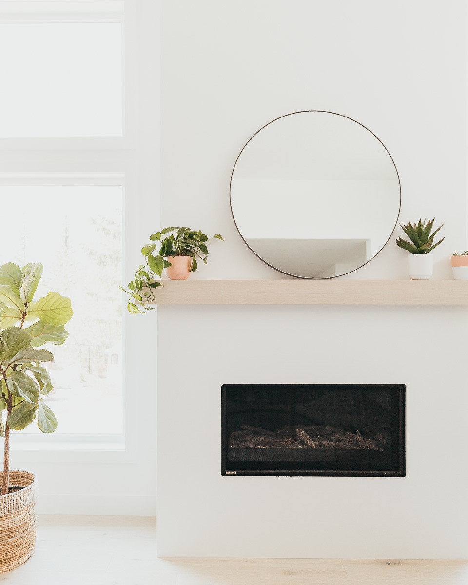 A modern fireplace with a white oak mantel and a round mirror.