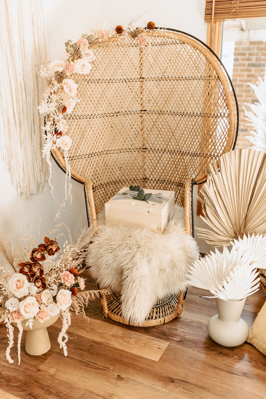 A beautiful custom baby shower gift keepsake box for a baby sits on a rattan wicker chair that is decorated with flowers and pampas grasses.