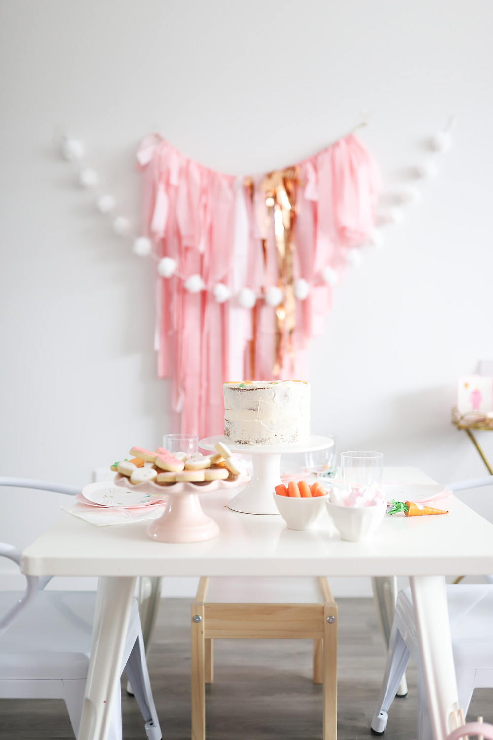 A room decorate with pink garlands and white pom poms for a little girls bunny birthday party at Easter.