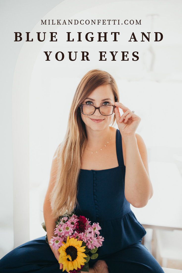 Girl wearing glasses and holding flowers looking at camera
