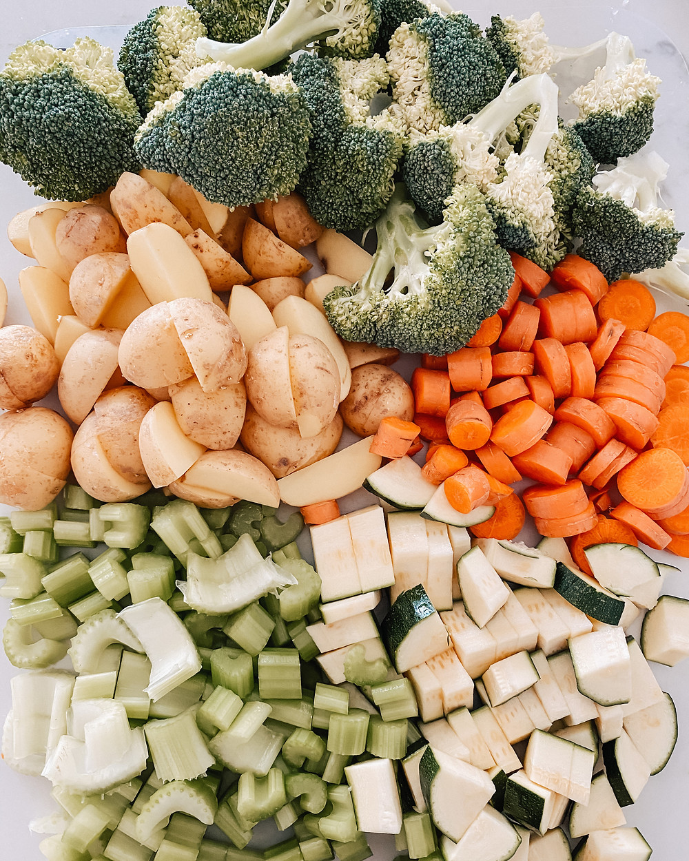 A group of vegetables containing broccoli, potatoes, carrots, celery, and zucchini sit on a countertop.