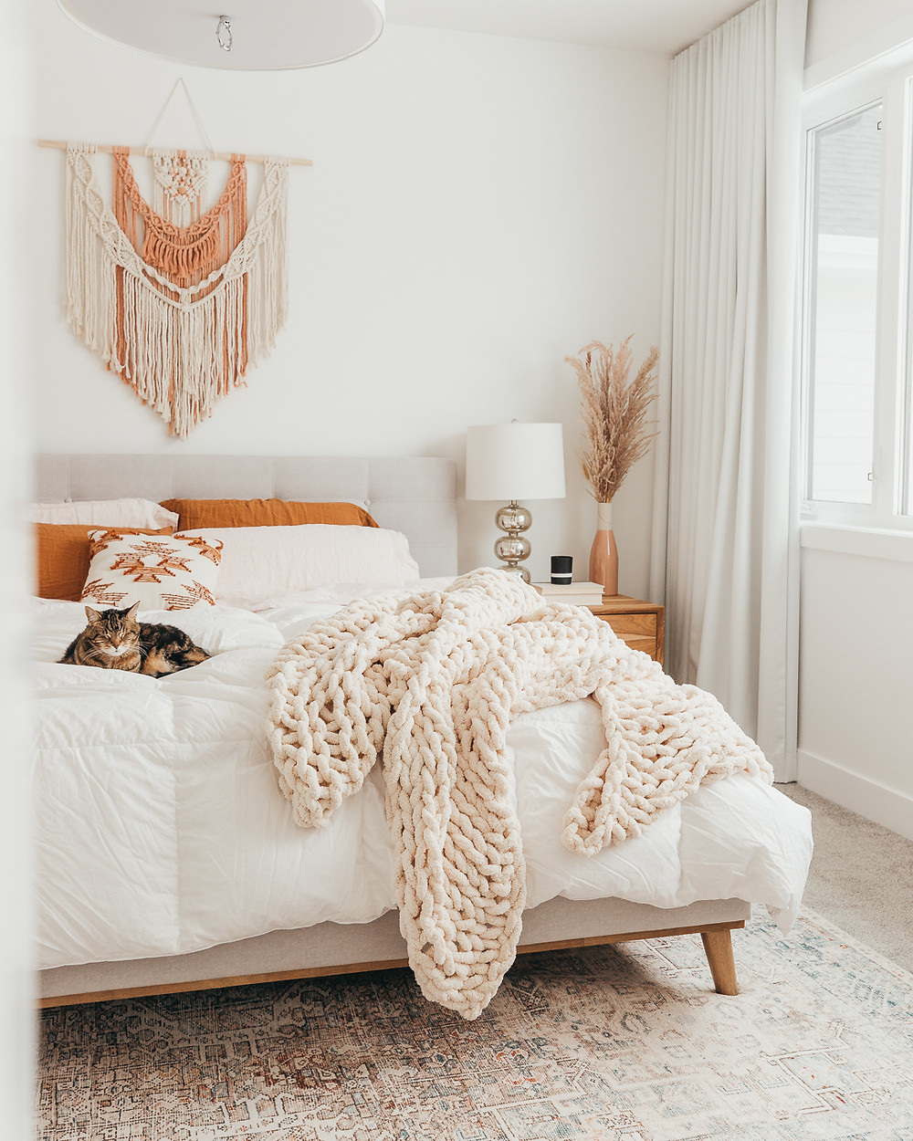 Cream and blush macramé wall hanging over grey fabric headboard rust and white sheets with chunky cream knit throw on bed sleeping cat mercury glass lamp on wood side table with pampas grass in vase natural light white drapes on window area rug under bed