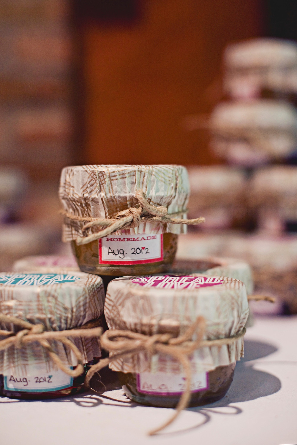 Homemade jam jars tied with twine are stacked as wedding favours at a rustic Italian inspired wedding.