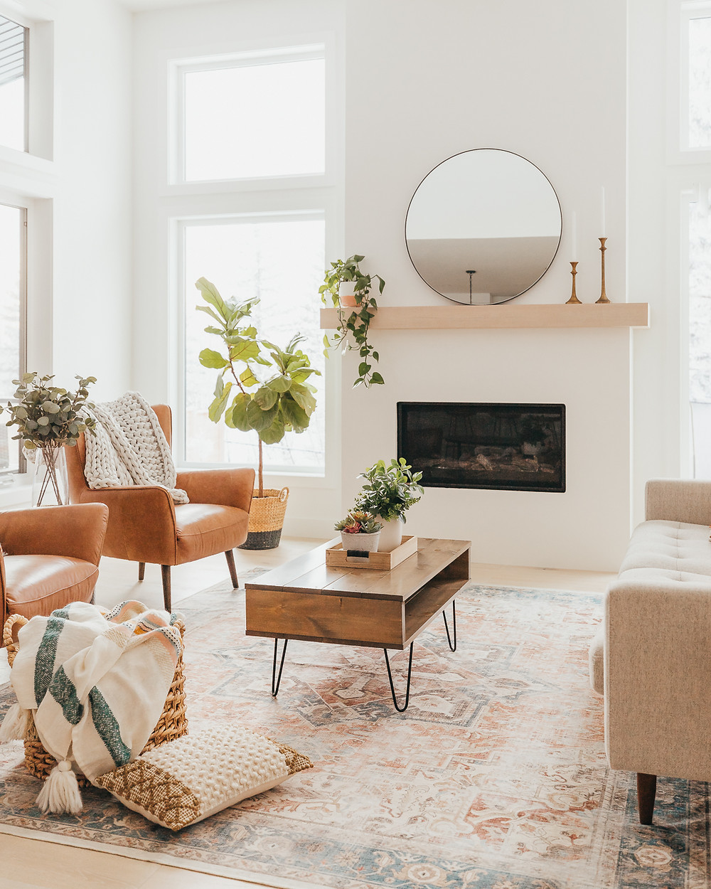 Two brown leather armchairs with chunky knit throw basket on floor with stripped blanket and textured throw pillow wood mantle with two candlesticks round black mirror hanging plant fiddle leaf fig in basket rectangular wood coffee table with black wood accents
