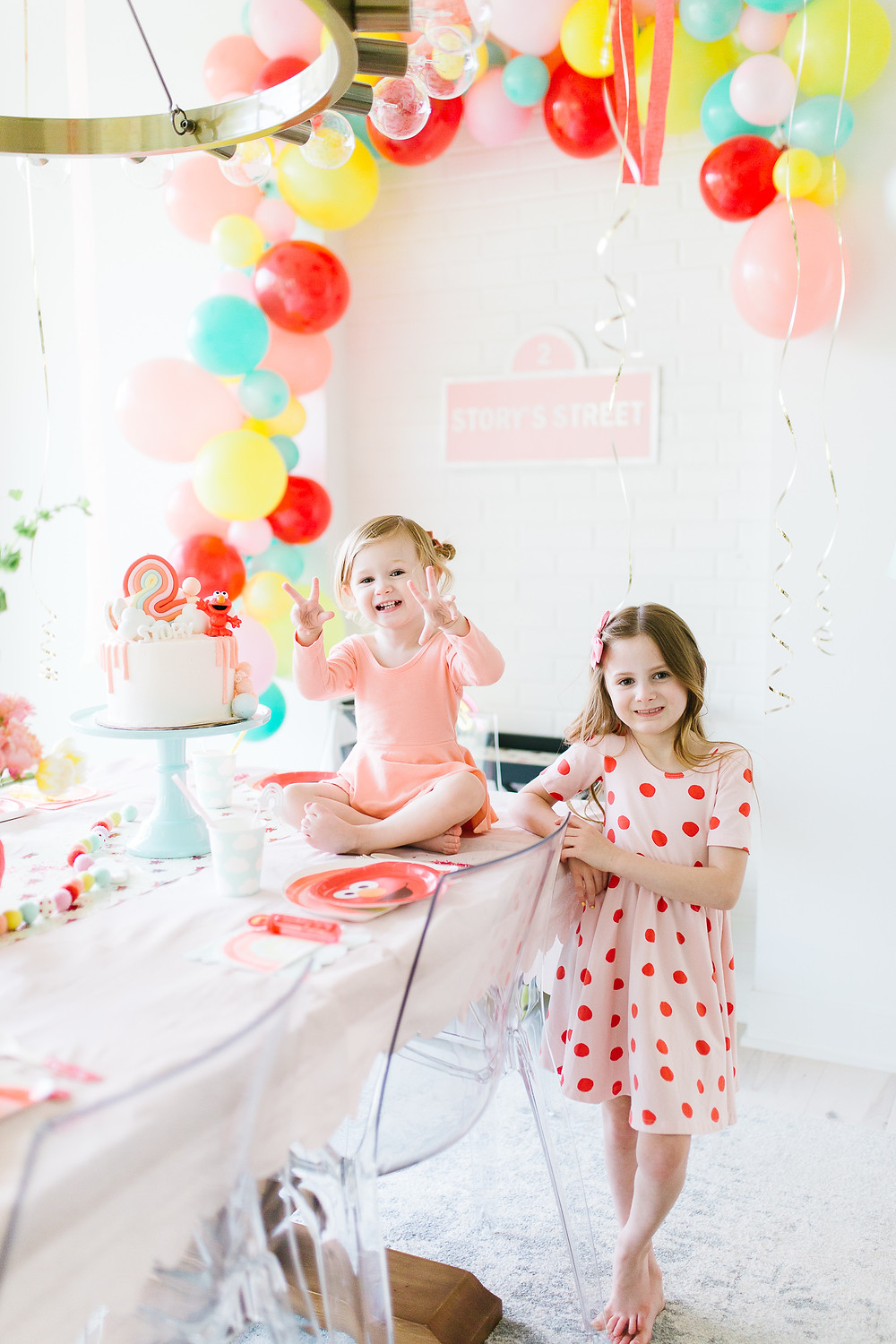A Sesame Street Elmo birthday party with Elmo tableware, colourful balloons and streamers hanging, a pink Elmo birthday cake, pink wall signage and an Elmo floral centrepiece.