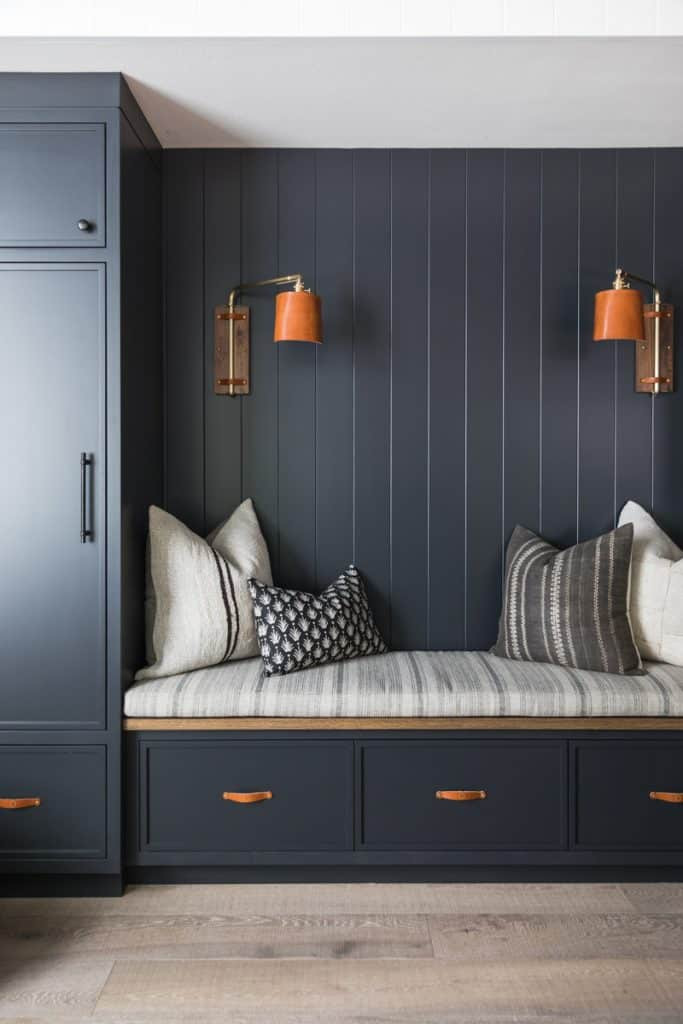 navy blue painted shiplap wall detail tall wall storage under bench drawer storage leather pulls orange shade swinging scones plaid striped throw cushions wide plant light hardwood floors