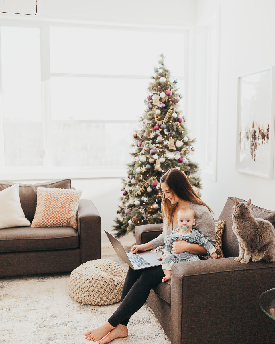 A mom sitting with her baby in the living room beside a Christmas tree working on her computer.