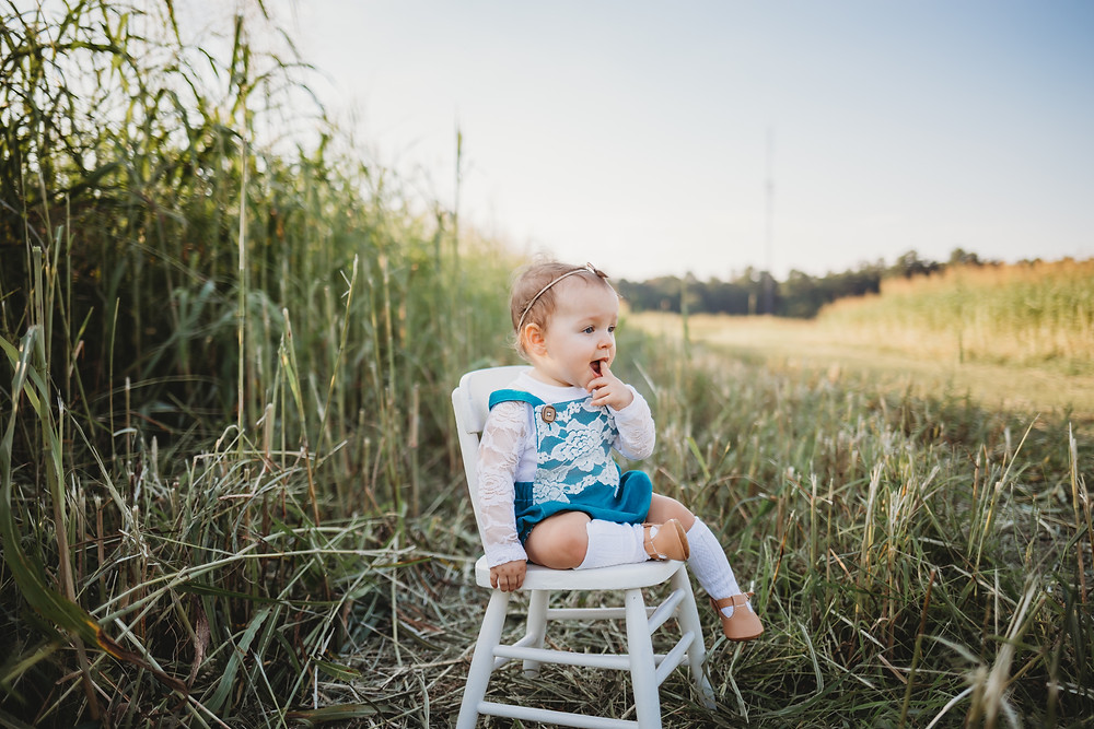 A little girl sitting on a white wooden chair wearing a blue lace and linen romper.