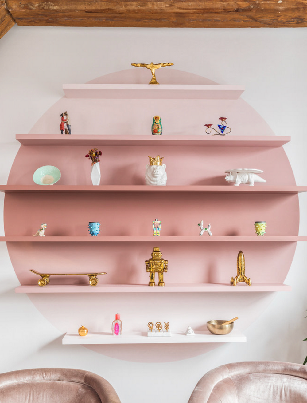 An ombre pink wall mural and shelves styled with gold and white accessories.
