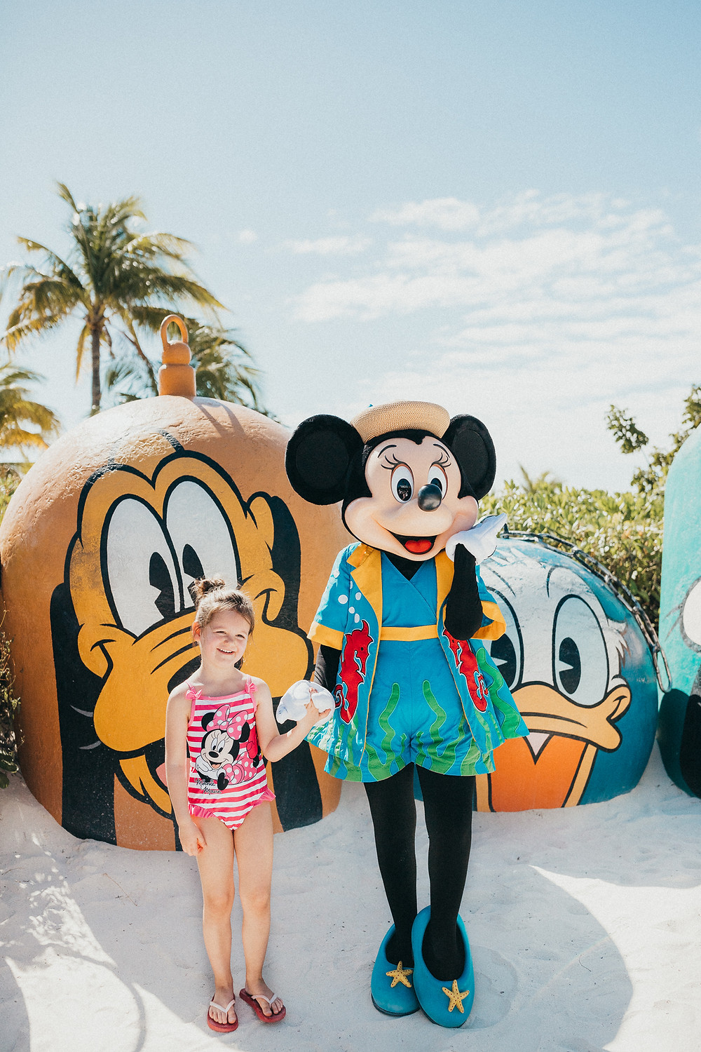 A little girl wearing a Minnie Mouse bathing suit standing with Minnie Mouse on the beach.