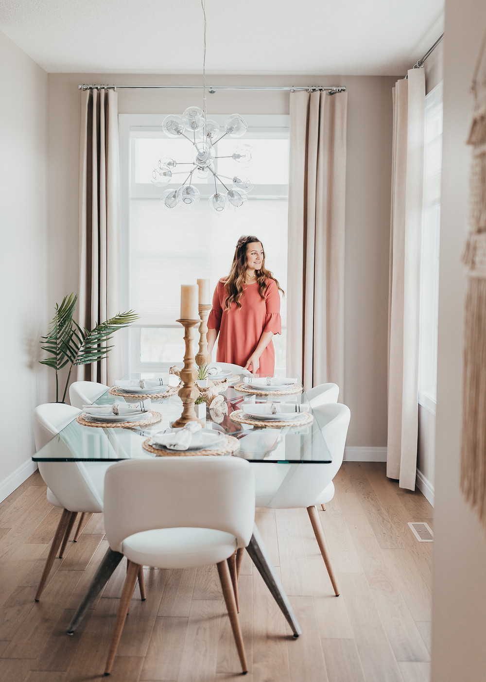 A girl standing in a modern dining room setting the table.