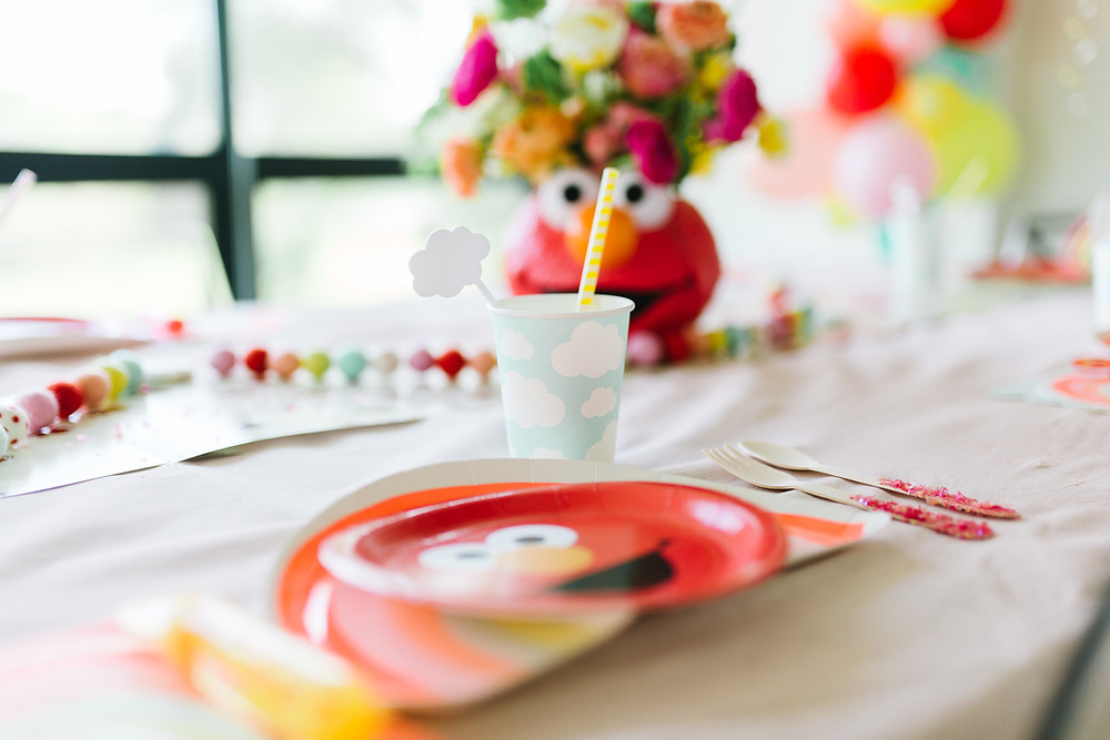 A Sesame Street Elmo birthday party with Elmo tableware including an Elmo plate, Elmo table runner, blue cloud paper cup, paper red strip straw, glitter fork and spoon, bubbles, rainbow napkin on a white table cloth with an Elmo floral centrepiece and colourful balloons and streamers.