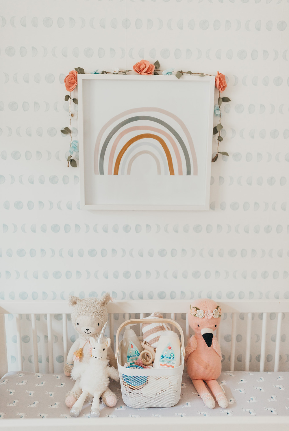Some baby products and stuffed animals sitting in a crib with a rainbow print framed on the wall behind.