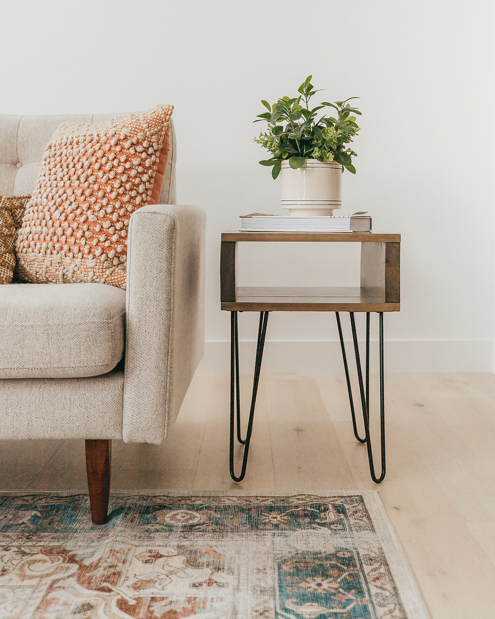 Wood sidetable with black accent legs book and plant area rug on natural wood floors cream color sofa with orange textured throw pillow