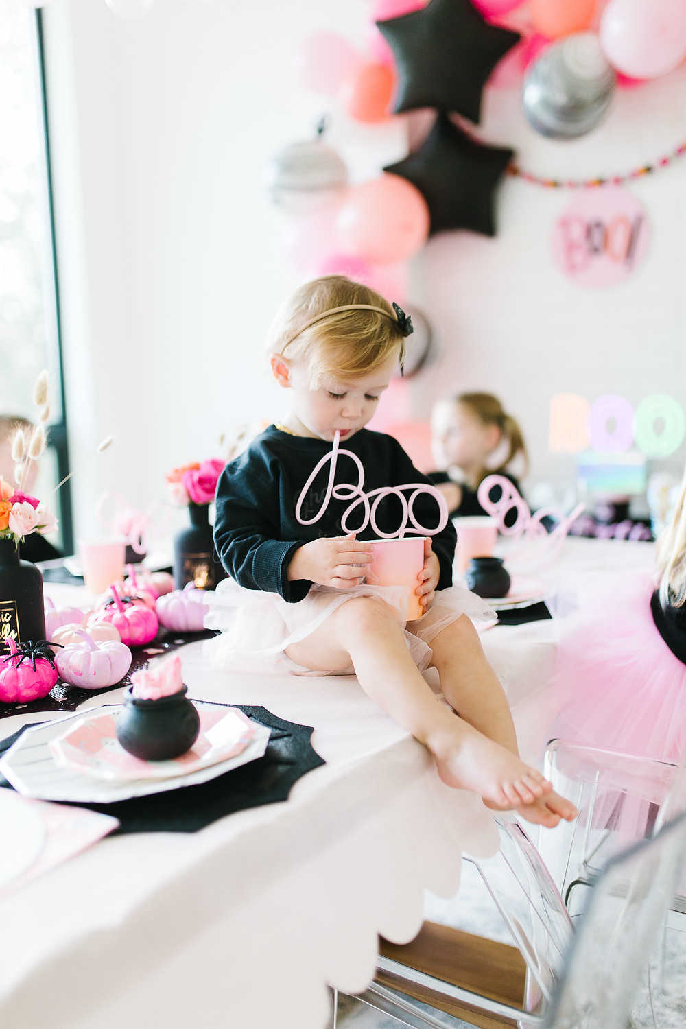 A baby sitting on a table drinking out of a BOO straw at a Halloween party with pink and black pumpkins.