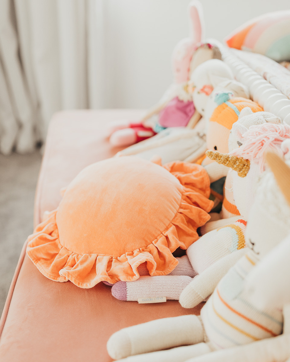 A circular pillow with ruffled edges sitting on a velvet bench next to some handmade cuddle and kind dolls.