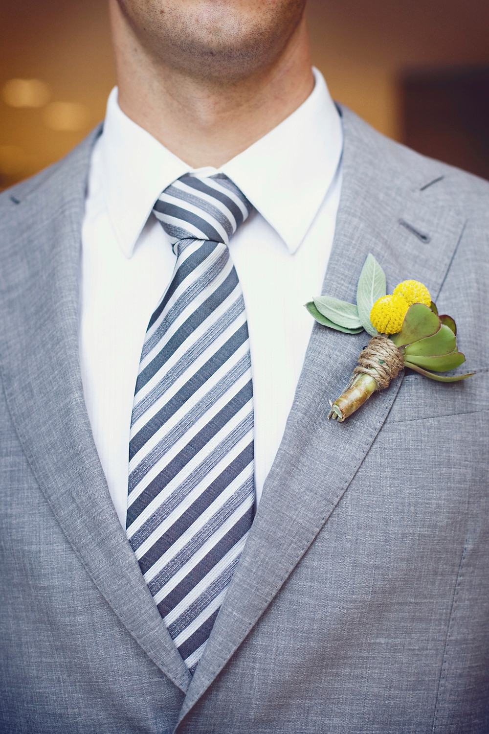 A groom wearing a grey suit is standing waiting for his bride on their wedding day.