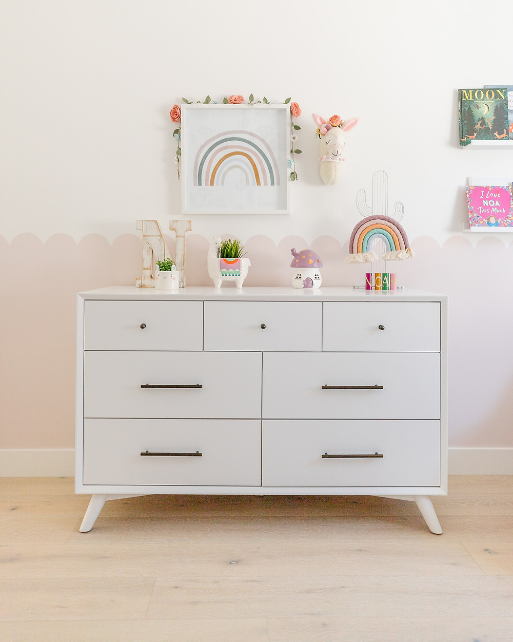 A white dresser in a little girls bedroom with white oak hardwood and boho accents in front of a scalloped pink wall.