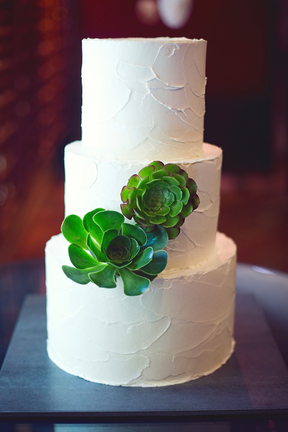 A rustic buttercream white wedding cake decorated with succulents on a wedding day.