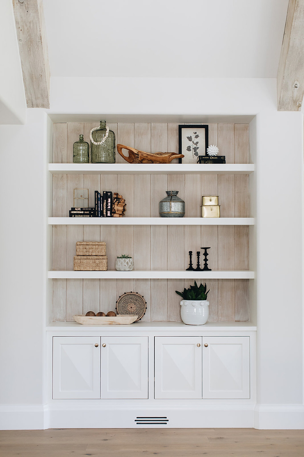 exposed wood beams vaulted ceiling built in cabinet with four doors white open shelves wood shiplap detail on wall with glass vase wooden box black framed picture candlesticks styling
