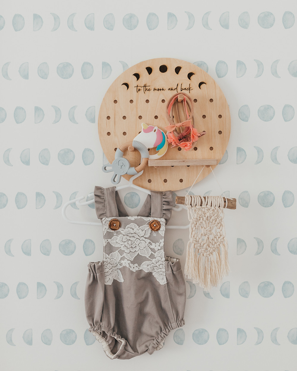 A wooden peg board with a lace and grey baby romper hanging from it.