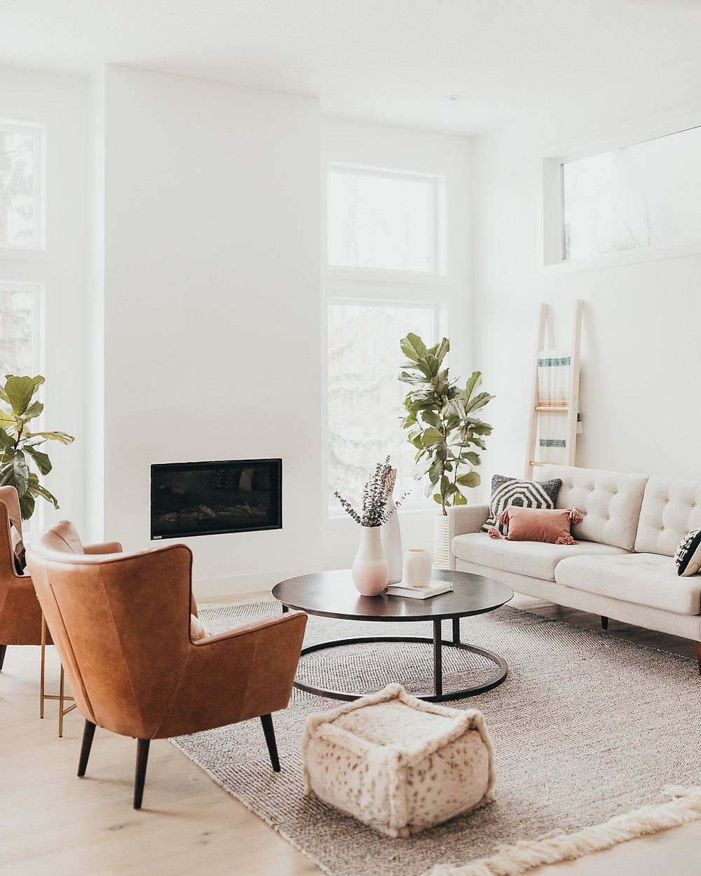 A white Scandinavian living room features a natural light wood floor with a natural fibre striped rug, metal round metal coffee table, two brown leather chairs, fur pouf, light sofa with pillows, blanket ladder, two fiddle leaf fig plants and a linear fireplace.