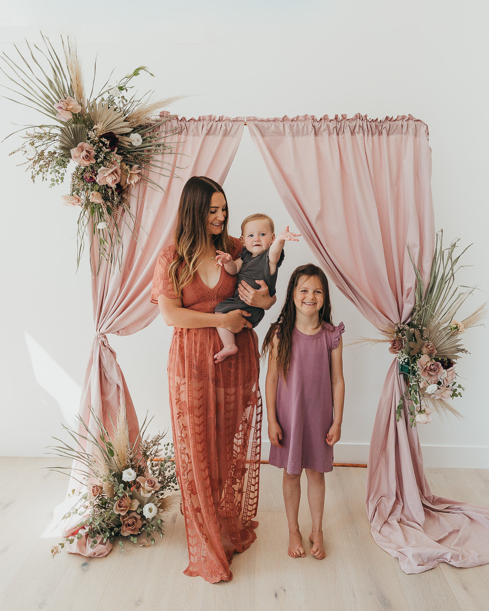 A mom and her two daughters are standing in front of a floral back drop at a party wearing pretty dresses with flowers behind them.