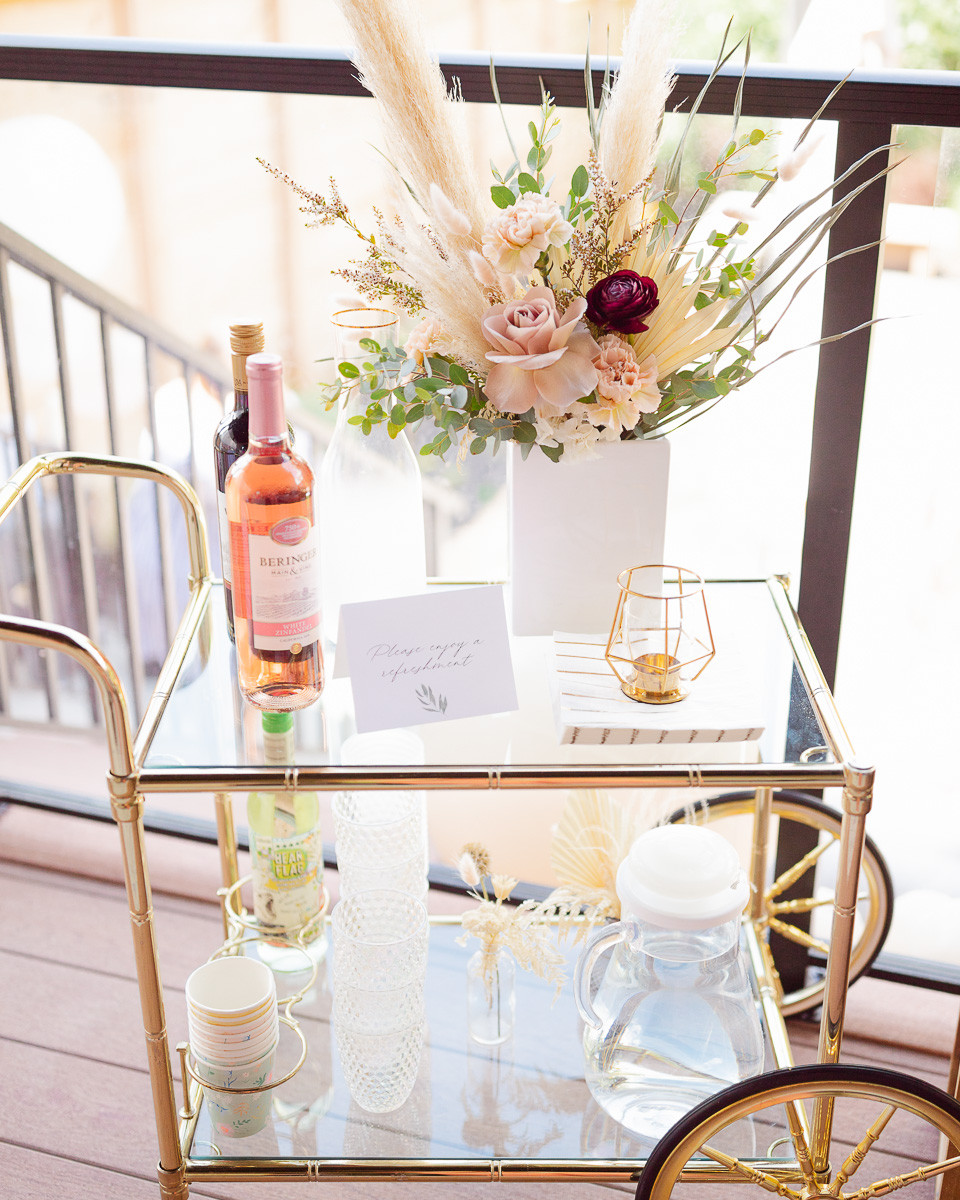 A vintage gold bar cart at a party with some wine and beautiful flowers in a white vase.