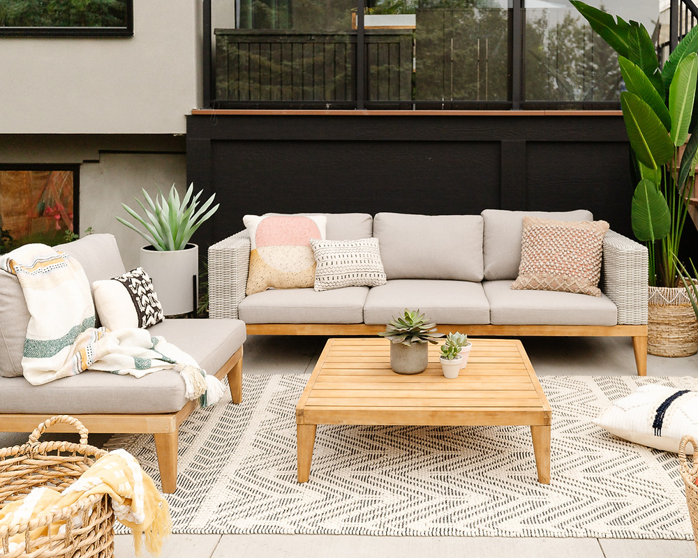 Backyard concrete patio elevated deck with black glass railing sofa with beige cushions and throw pillow accents in coral yellow chair with striped throw blanket potted plants wicker basket with blankets potted succulent plants wicker basket with bird of paradise