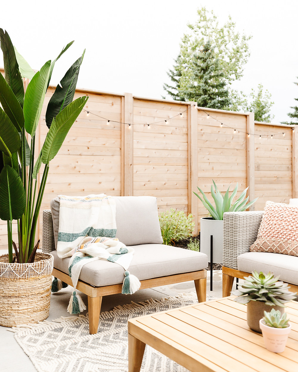 Modern outdoor Wicker sofa with wood accents and beige cushions black and white area rug chair with wood accent and striped throw blanket wood accent table with succulent pots wicker basket with blankets patterned oversized pillow on rug potted plant wood fence landscaping perennial flowerbed backyard concrete patio space