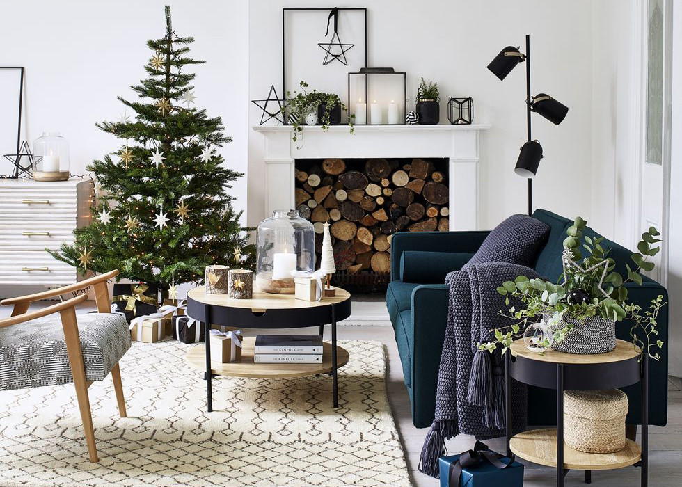 A Scandinavian Nordic living room decorated with minimal and modern holiday christmas decor with a simple christmas tree, white fireplace, black accents, a velvet sofa and a white rug.