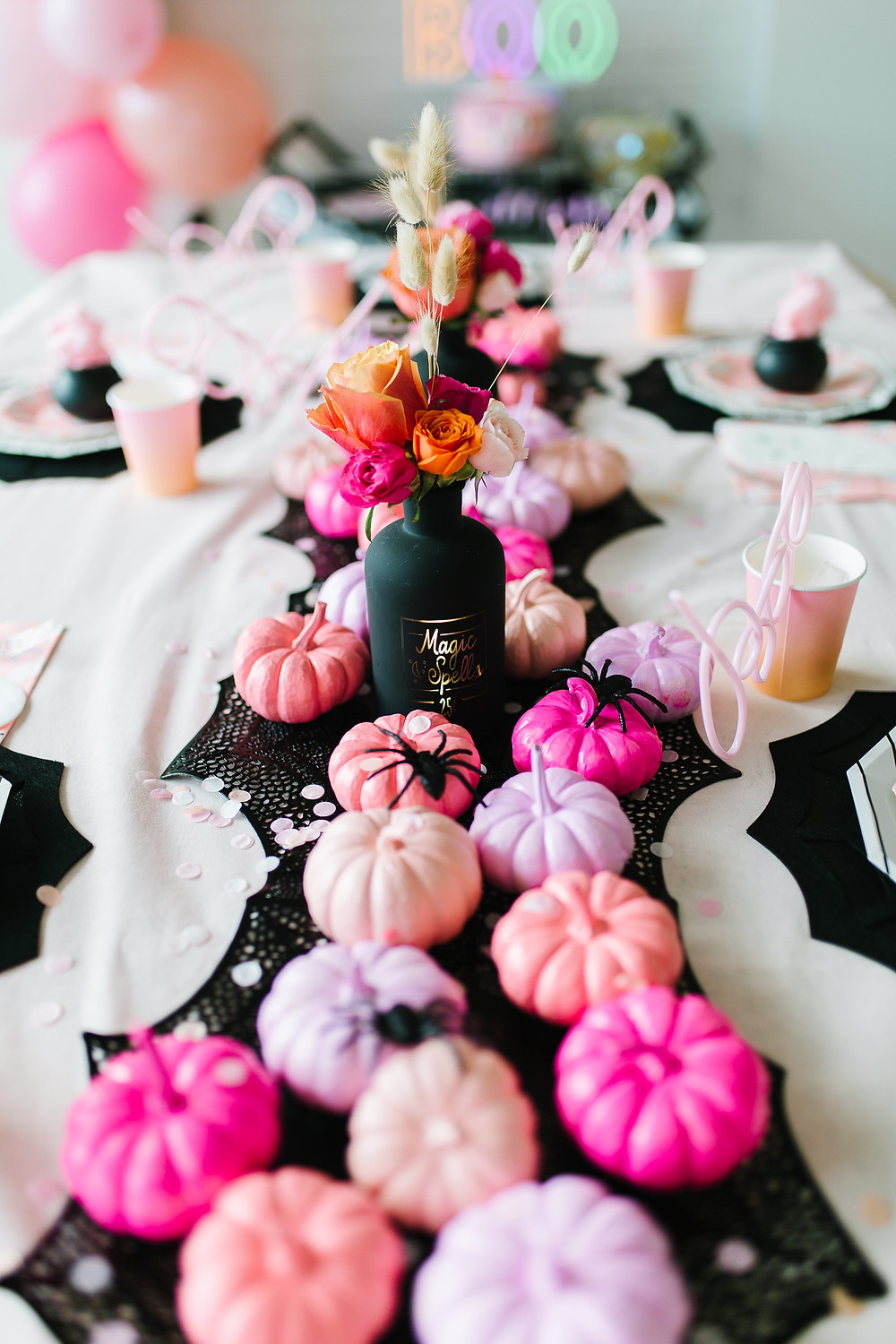 Ghoul gang halloween party with a tablescape of Halloween decor including pink and orange painted pumpkins and flowers.
