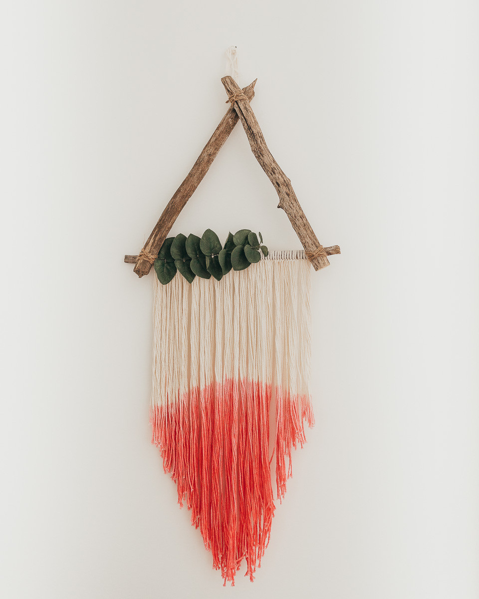 A triangle wall hanging with eucalyptus leaves and coral yarn.