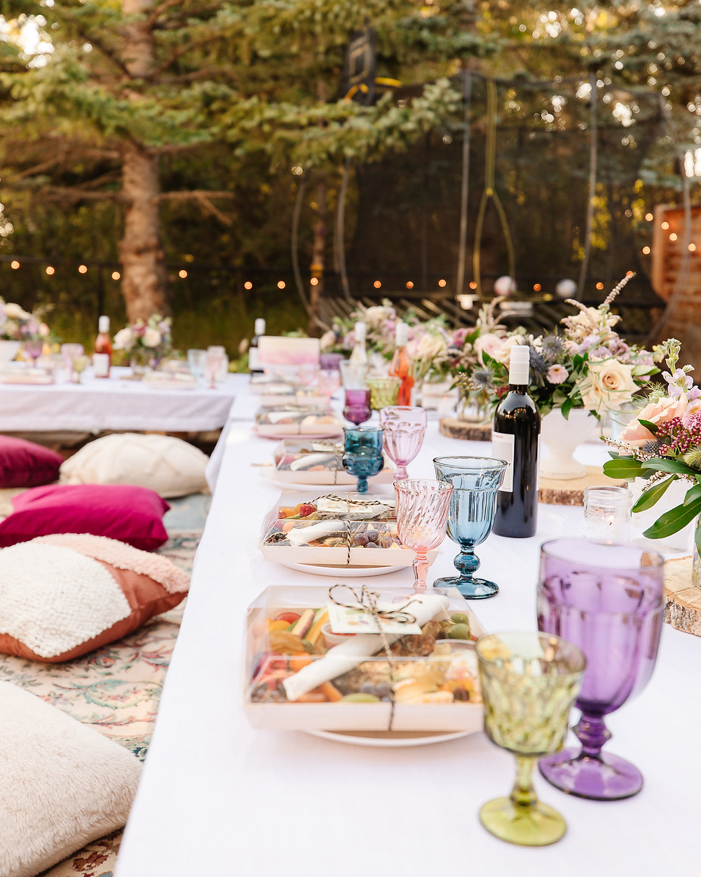 An evening backyard boho garden party with gorgeous flowers, vintage rugs, charcuterie wine, twinkle lights, coloured glasses, velvet throw pillows, boho decor and all your best girlfriends.