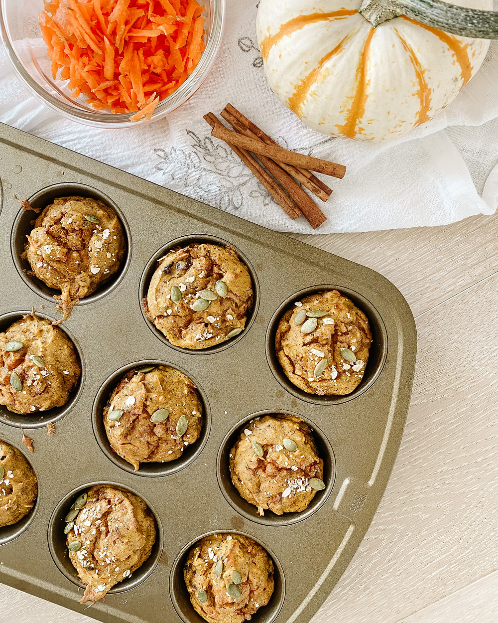 A metal muffin tin on a white table cloth shows off pumpkin and nut muffins beside cinnamon sticks, a white pumpkin and a bowl of carrots.