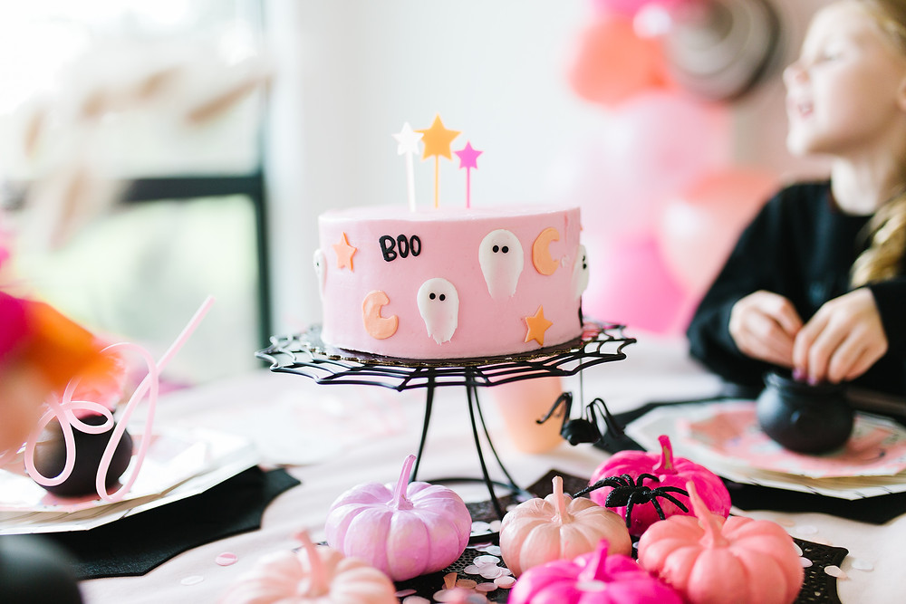 A haunting halloween cake in pink pastel at a ghoul gang Halloween party.
