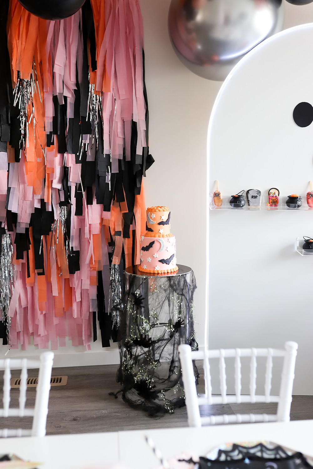 A children's halloween themed party with pink, orange and black streamers hanging on the wall with metallic balloons next to a children's white table covered in spiders and a starry bat themed cake, and a miniature tombstone.