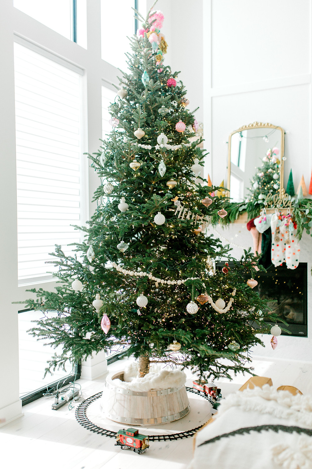 A Christmas tree decorated with metallic and pink ornaments and a decorated fireplace in the background with a gold framed mirror, mini Christmas trees, garland and stockings.