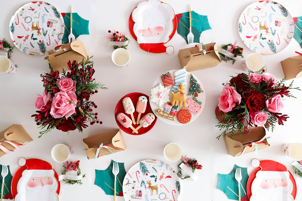 A Christmas tablescape at a kids Christmas party set up with red, mint and pink paper plates in the shape of Santa next to holiday flowers and Christmas cookies.