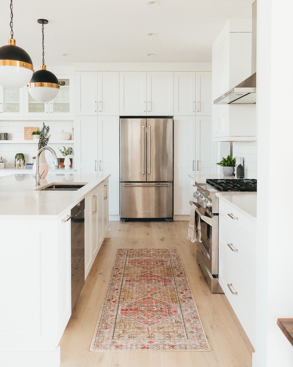 A kitchen with white cabinets, white oak floors, and black pendant lights with a blush runner.