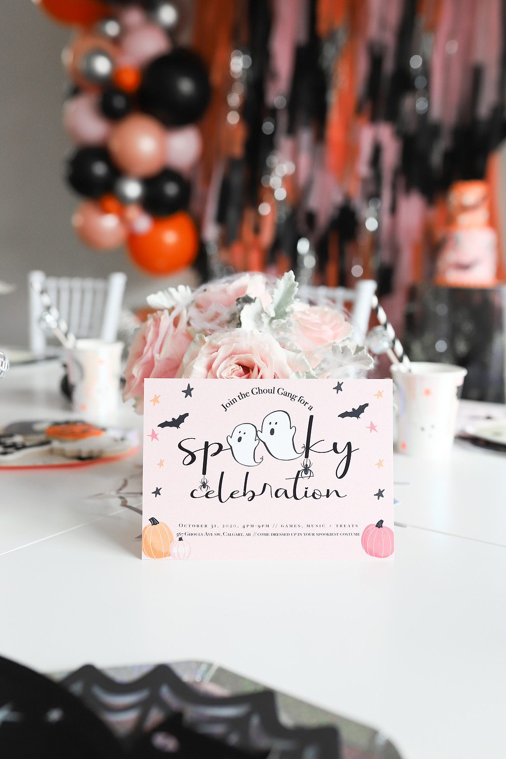 Children's spooky Halloween decor with orange and black party decorations with pink roses and invitations on a table.