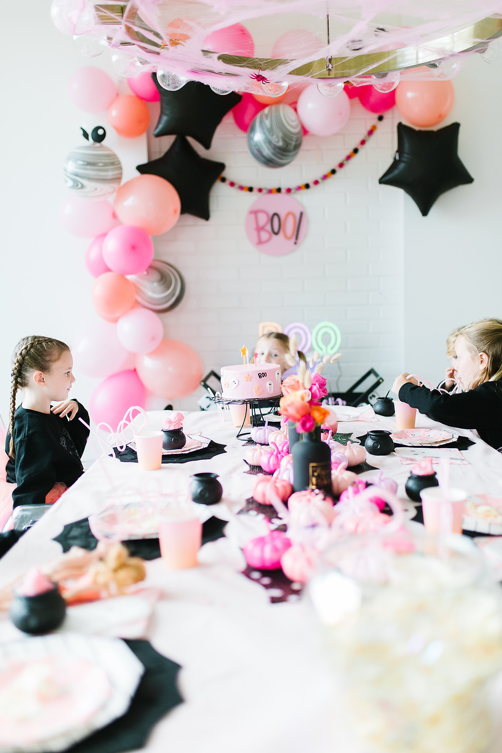 Ghoul gang halloween party tablescape of Halloween decor including pink and orange painted pumpkins, balloons and flowers.