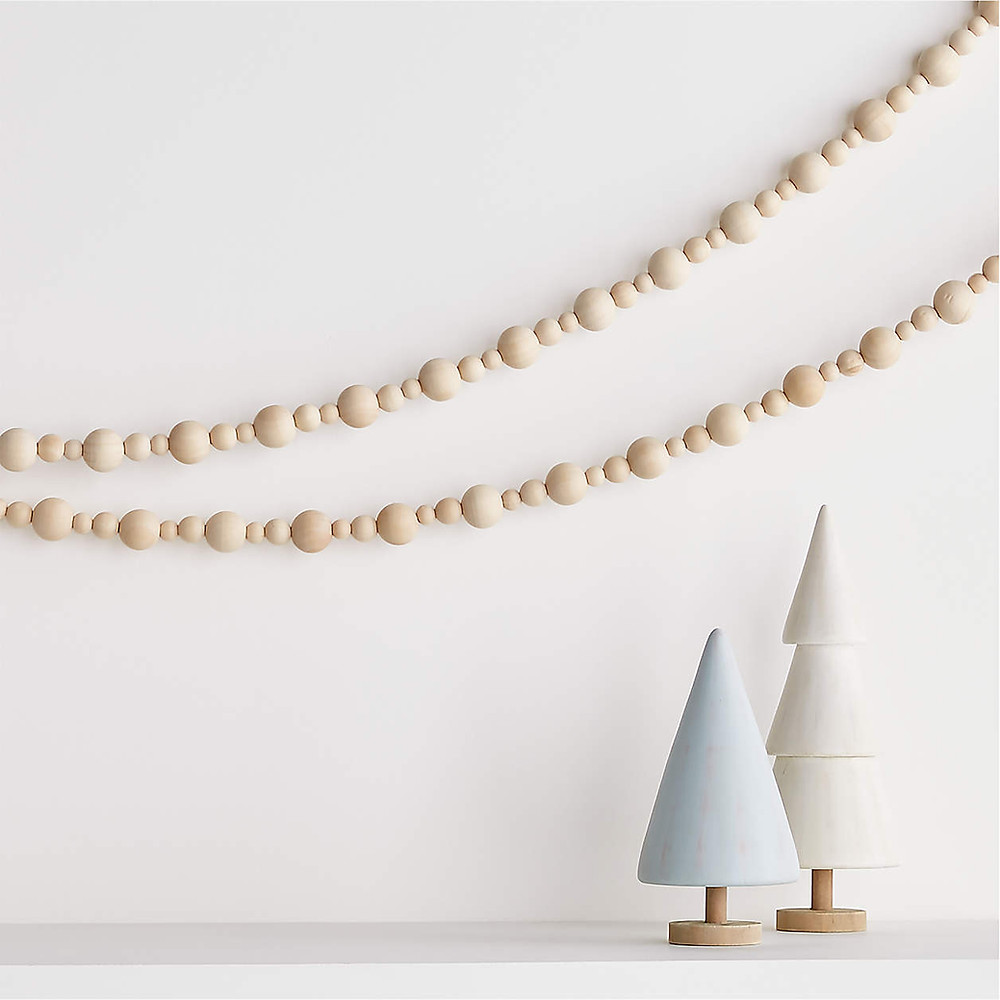 A simple natural wooden beaded garland strung above modern scandinavian wooden Christmas tree decorations sitting on a fireplace mantel.