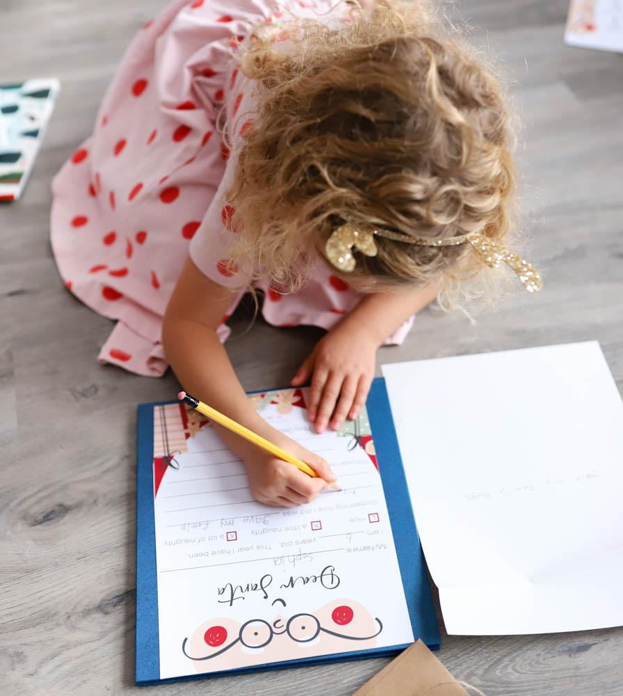 A little girl on the floor writing a letter to Santa.