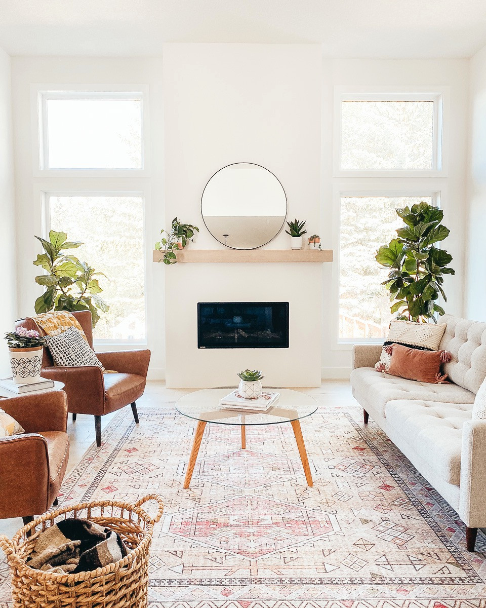 A modern mid century style living room with a large blush and gold area rug in front of a minimal linear white fireplace with a white oak mantle.